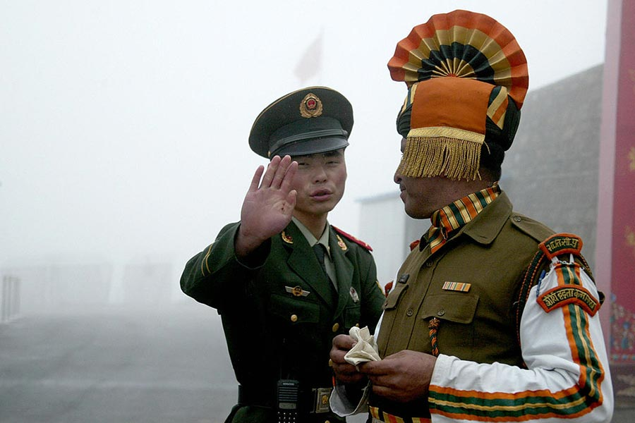 6月底中印發生對峙的乃堆拉山口(Nathu La Pass)位於不丹、印度、中國邊境交界處,附近的洞郎或稱都克欄高地被認為戰略價值重大。圖為2008年拍攝的中印雙方邊境人員。(DIPTENDU DUTTA/AFP/Getty Images)