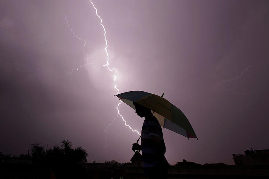 天空雷電交加,一名行人在雨中行走。(RAKESH BAKSHI/AFP/Getty Images)