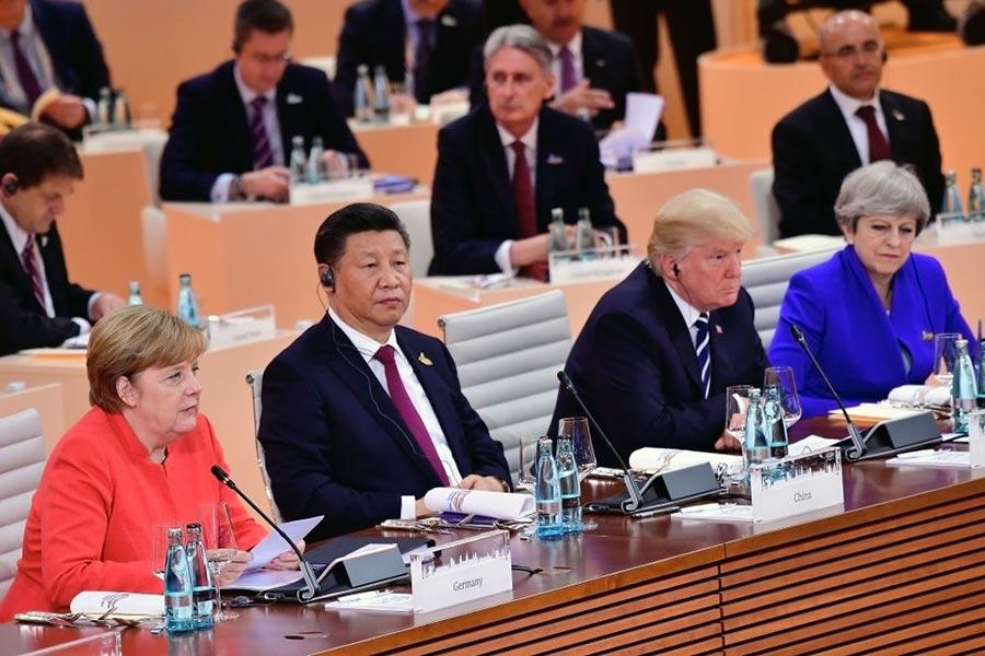 圖為今年7月7日的G20會議上,東道主德國總理默克爾旁邊是中國主席習近平、美國總統特朗普和英國首相文翠珊。(Thomas Lohnes/Getty Images)