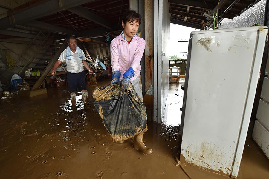 日本南部的暴雨及洪水造成的死亡人數攀升至15人,另至少有14人失蹤。圖為2017年7月7日,日本九州福岡朝倉市,民眾清理家中。(KAZUHIRO NOGI/AFP/Getty Images)