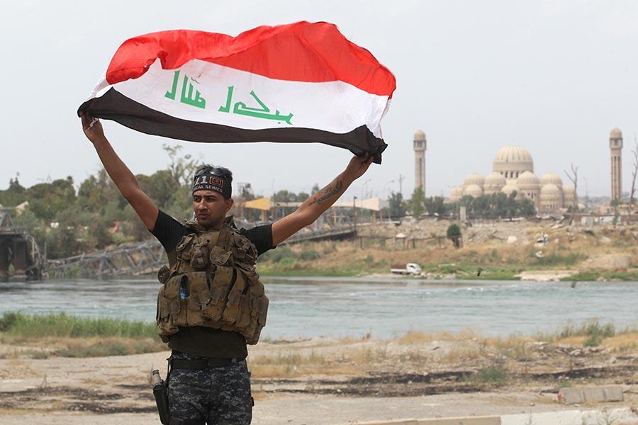 美國總統特朗普對伊拉克、伊拉克總理和伊拉克保安部隊表示祝賀,祝賀他們將摩蘇爾(Mosul)從伊斯蘭國(IS)激進份子手中解放出來。圖為一名伊拉克警員在摩蘇爾舉起伊拉克國旗,以示摩蘇爾的勝利。(AHMAD AL-RUBAYE/AFP/Getty Images)