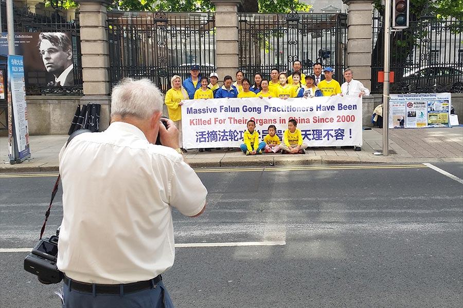 7月6日,愛爾蘭議會舉行「中共活摘法輪功學員器官」發佈會,部份愛爾蘭法輪功學員在議會外聲援,全國大報《愛爾蘭獨立報》(Irish Independent)攝影記者在現場進行報道。(視像擷圖)