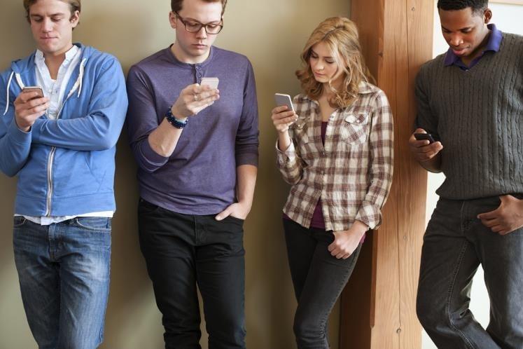 朋友見面不知道怎麼聊天,只好各自低頭滑手機,「我們當面聊天的功能竟然退化了?」(Getty Images)
