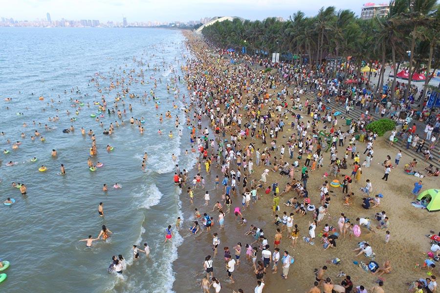 今年夏季大陸酷熱,很多人早早的就去海邊。圖為5月30日的海口海灘。(STR/AFP/Getty Images)