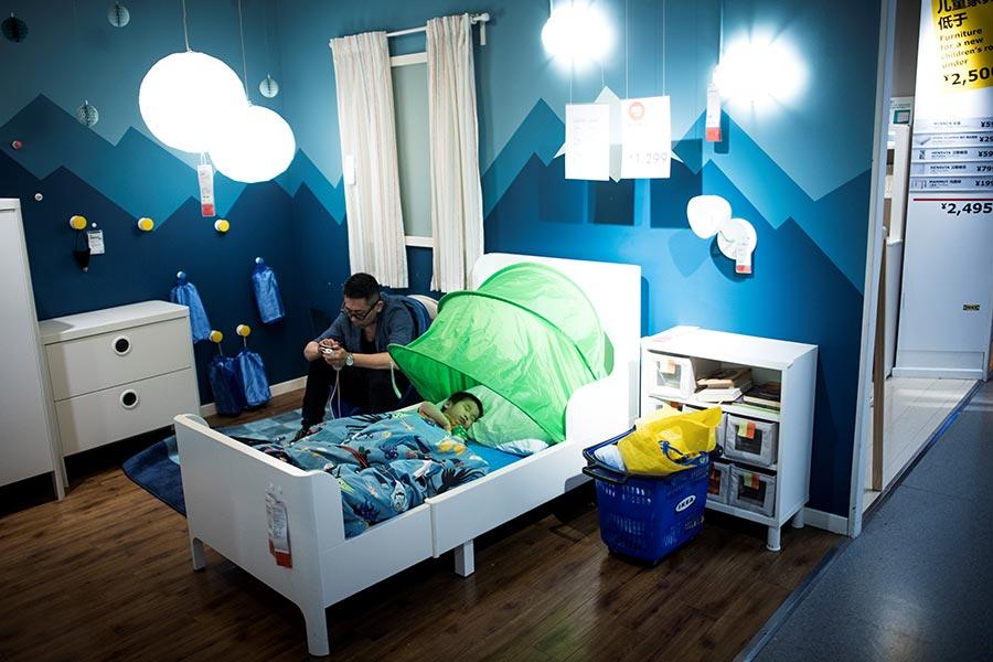 圖為7月5日,上海居民帶著孩子到市中心的Ikea商店來睡覺。當天溫度36.2攝氏度。(JOHANNES EISELE/AFP/Getty Images)