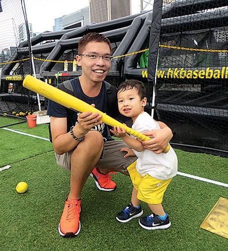 李先生和兩歲兒子一起打棒球。(張小慧/大紀元)