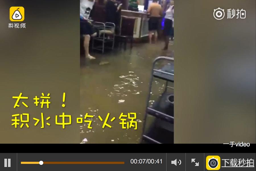 圖為長春市民在火鍋店的積水中吃火鍋。(視像擷圖)