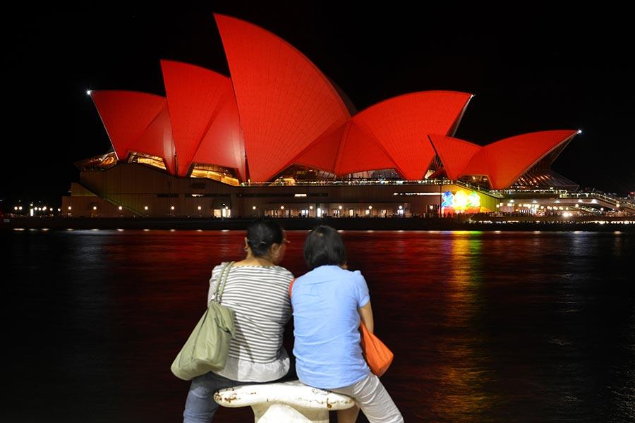 圖為2016年2月8日,澳洲悉尼歌劇院為慶祝中國新年,打出紅色燈光把歌劇院外牆染紅。(PETER PARKS/AFP/Getty Images)