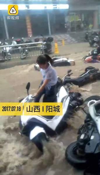一名騎電單車的女士也被衝倒在水中,只好棄車。(網絡圖片)