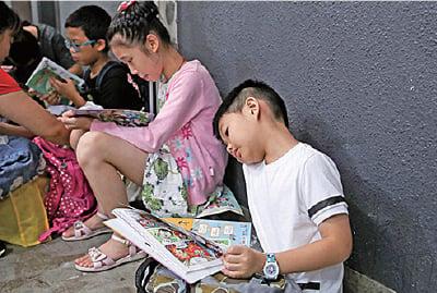 小朋友買到新書後,急不及待坐在場邊閱讀。