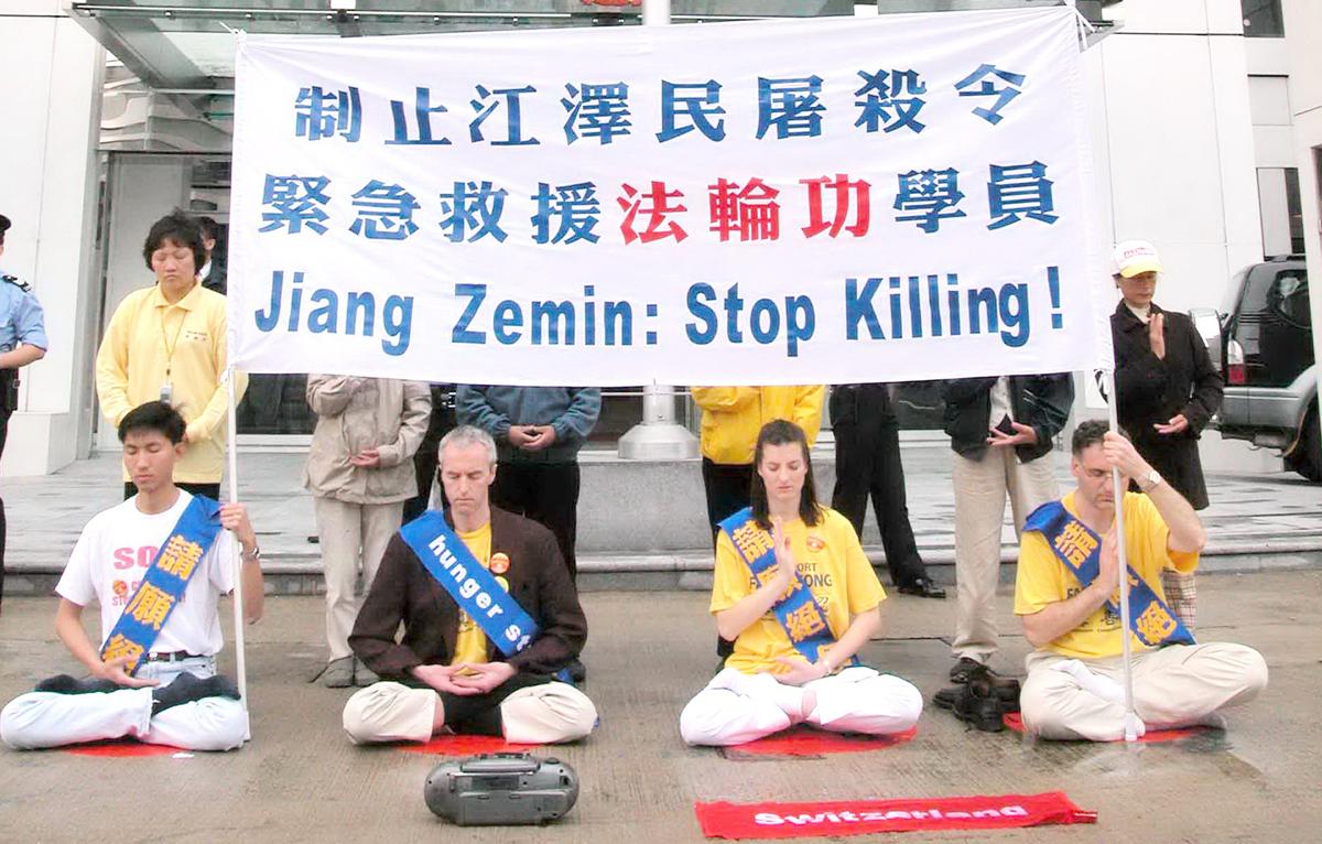 2002年3月14日,4名瑞士法輪功學員和12名香港學員在中聯辦正門前靜坐請願,遭警方武力抬走及拘捕,控以「阻街」等7項罪名。經過3年多的訴訟,香港終審法院時任首席法官李國能等5位大法官,在2015年5月6日一致裁定警方的拘捕行動不合法,法輪功學員的控罪全部被推翻。(大紀元資料圖片)