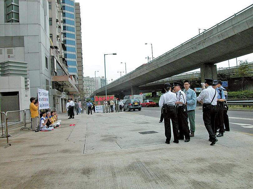在中聯辦門前靜坐請願的16名法輪功學員,佔有行人道的空間很少,反而是警方用鐵馬把行人道兩邊封鎖,不讓行人通過。(大紀元資料圖片)