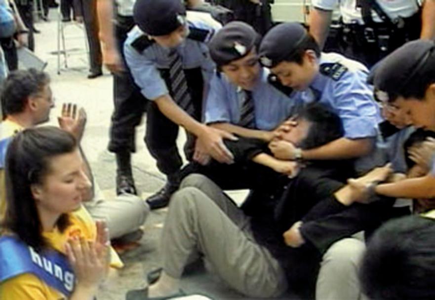 16名當日在中聯辦外請願的法輪功學員,每人被四至五名警員粗暴地抓面、扯頭、按太陽穴等穴位,然後架起請願者的雙手雙腳抬上警車,送往警署。(大紀元資料圖片)