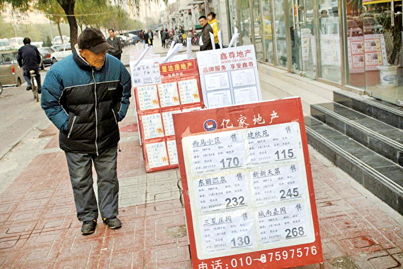 中國房地產真的到了變天的時間段。大佬、富人們正在有步驟地退出。圖為北京一市民在房產中介門口看房屋價格牌。(GOU YIGE/AFP/Getty Images)