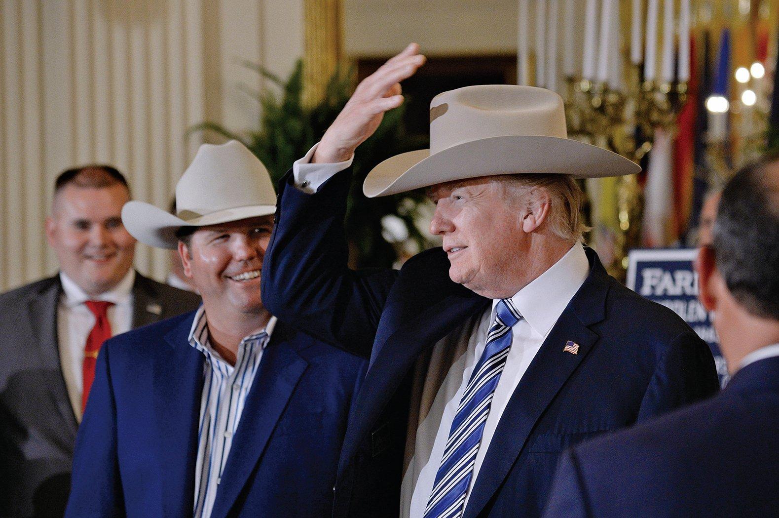 7月17日美國總統特朗普在白宮出席美國製造周活動。圖為特朗普頭戴美國產的「斯泰森帽」與廠商交談。(AFP)