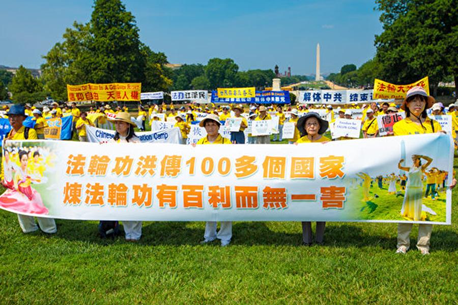法輪功學員手舉橫幅「法輪功洪傳100多個國家 煉法輪功有百利而無一害」。(Mark Zou/大紀元)