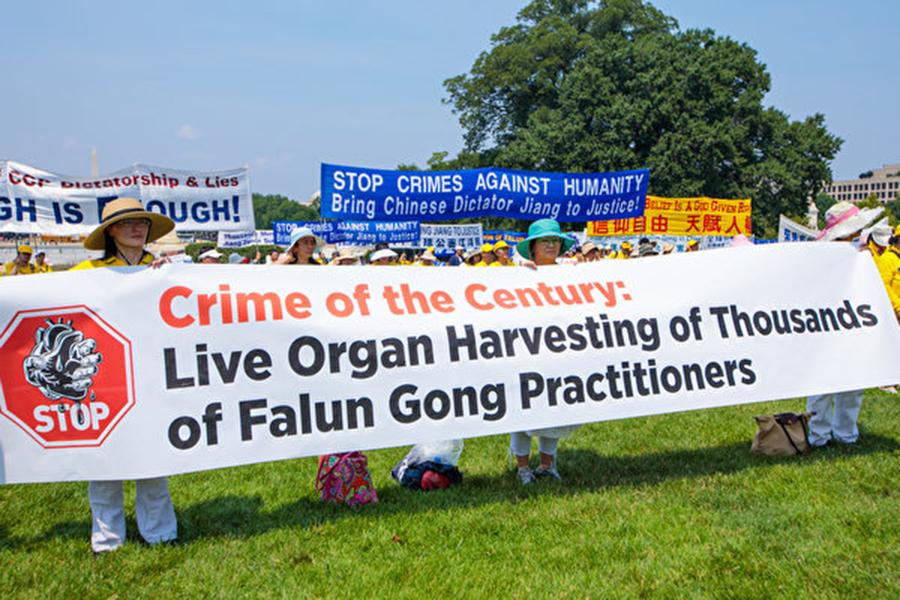 法輪功學員手舉英文橫幅,上書「國家犯罪:活體摘取法輪功學員器官」。(Mark Zou/大紀元)