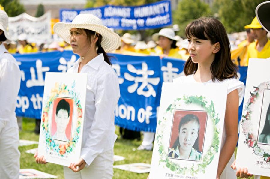 法輪功學員手捧照片,悼念被迫害致死的中國法輪功學員。(李莎/大紀元)