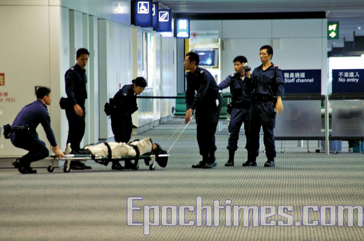 一名法輪功學員遭航警用施暴毯包裹並丟上平台車,強行送上飛機。(大紀元)