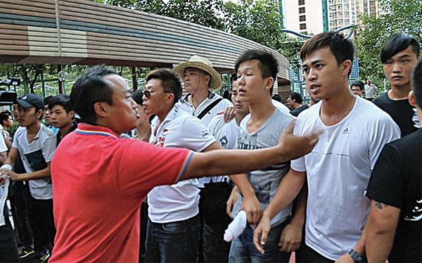 2013年8月,梁振英到天水圍出席地區論壇,場外出現大批戴上口罩的金毛、紋身青年不斷向反梁示威者挑釁。事後傳媒揭發這幫「黑色梁粉」來自天水圍區內多個社團。(大紀元資料圖片)