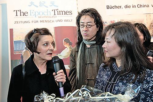 歐洲《大紀元》總編周蕾(右一)向赫塔穆勒(左一)贈送《九評共產黨》和中國著名人權律師高智晟的傳記《神與我們並肩作戰》。(攝影/吉森)