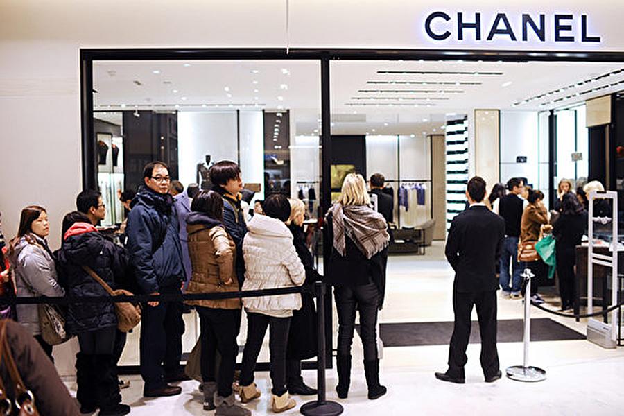 法國巴黎一間CHANEL,民眾排隊準備入內購物。(MARTIN BUREAU/AFP)