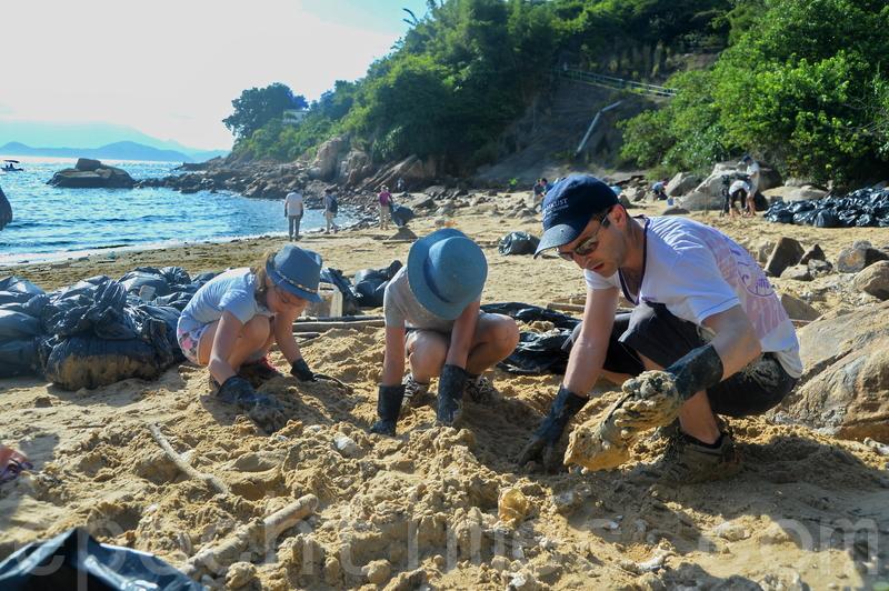 來自巴黎、已在香港居住兩年的Thomas帶著兩個女兒一起清潔海灘。(宋碧龍/大紀元)