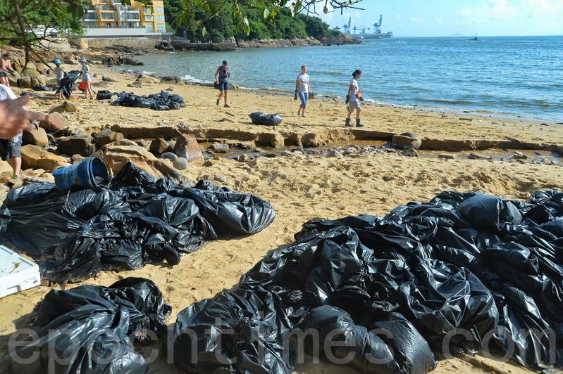 昨日有近百名市民,到南丫島的海灘清理棕櫚硬脂,清理出來的棕櫚硬脂被裝進黑色的大型垃圾袋。(宋碧龍/大紀元)