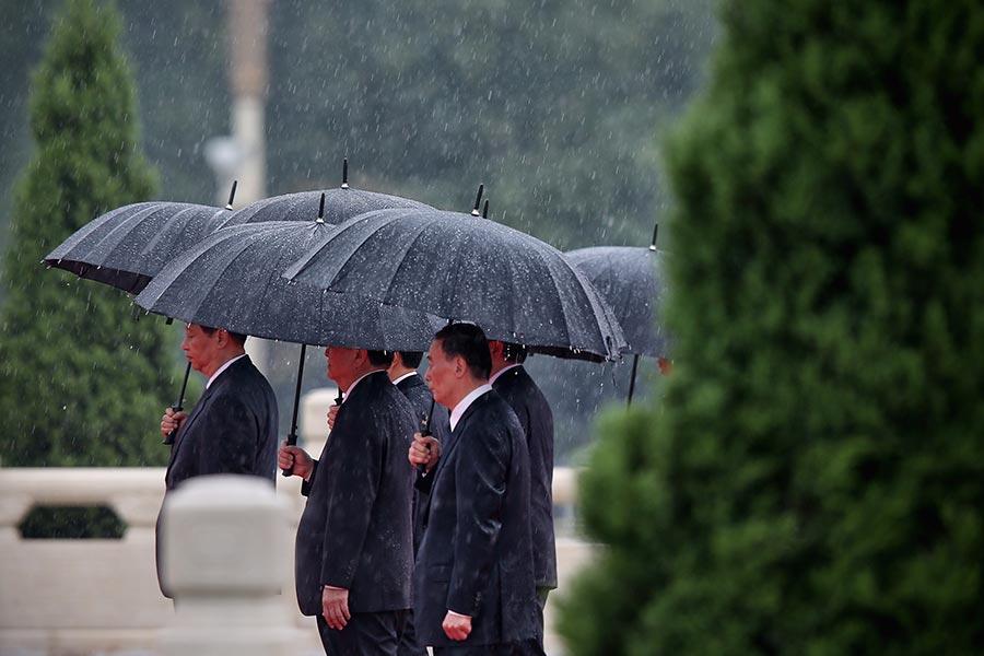 2013年10月習近平、王岐山在北京天安門撐傘前行。(Feng Li/Getty Images)