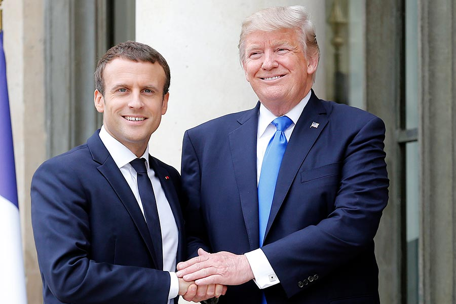 7月13日,美國總統特朗普(右)在巴黎愛麗舍宮前,與法國總統馬克龍在會面前握手合影。(Thierry Chesnot/Getty Images)