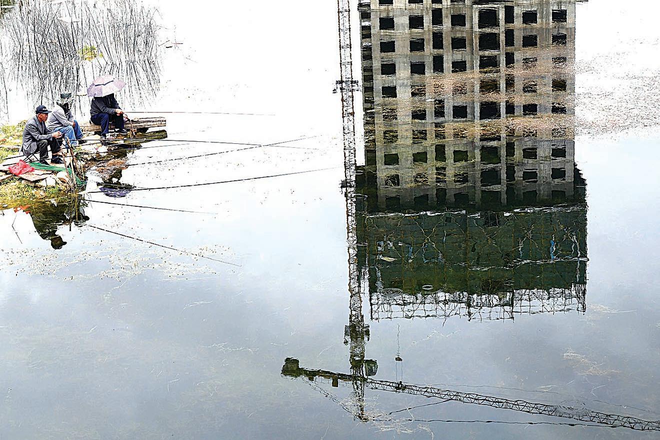 雲南被擱置8年的下馬村城中村改造項目近日傳出重新啟動。圖為昆明民眾在已經成魚塘的工地上釣魚。(大紀元資料室)