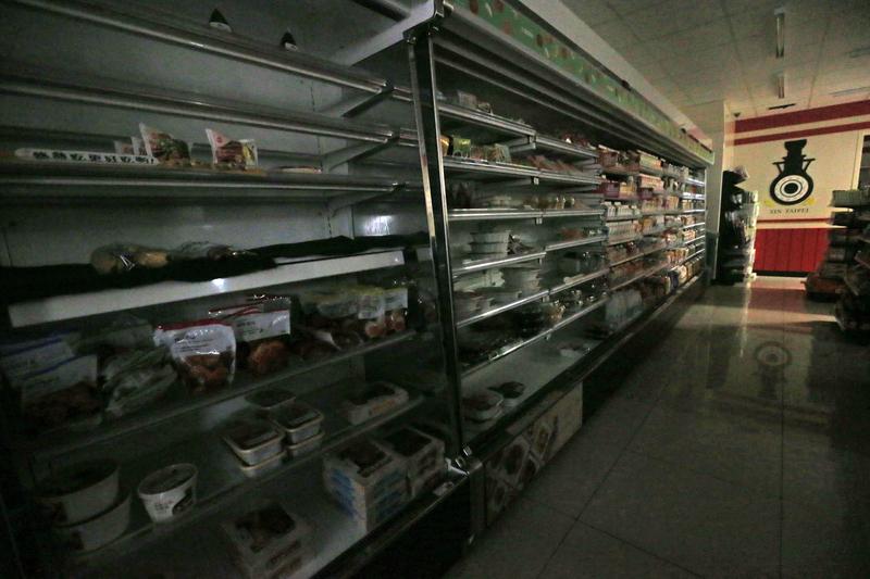 台北市一家超商停電,店內一片黑,冷藏商品區也受影響。(中央社)