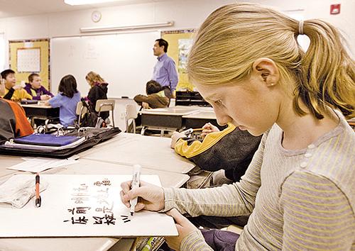 歐洲和美國等地,中文已成為必學語言。圖為美國馬里蘭州中文學校裏,外國女孩學習寫李白的詩。(AFP)