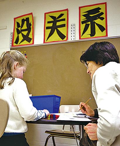 許多歐美家長讓子女從小就學習中文,不少美國中小學也已開辦中文課。圖為美國馬里蘭州Potomac一所中文學校裏的老師正在教兒童寫中文。(AFP)