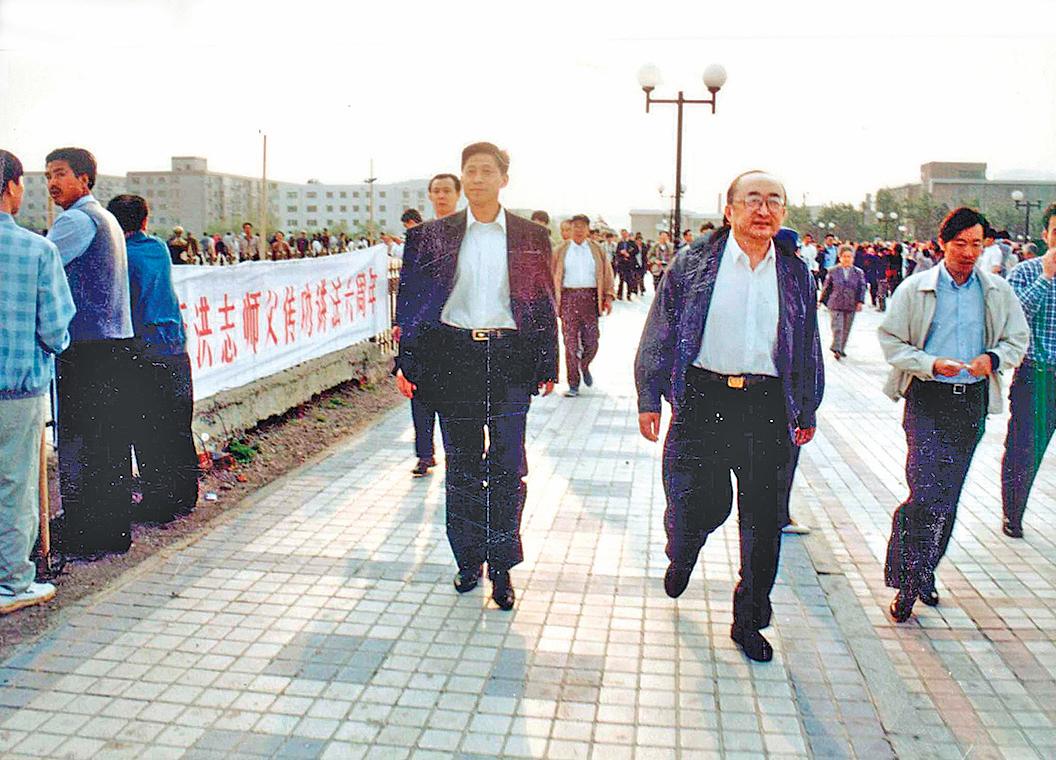 1998年時任中國國家體委主任伍紹祖(右圖: 中)考察時長春法輪功學員集體煉功場面。