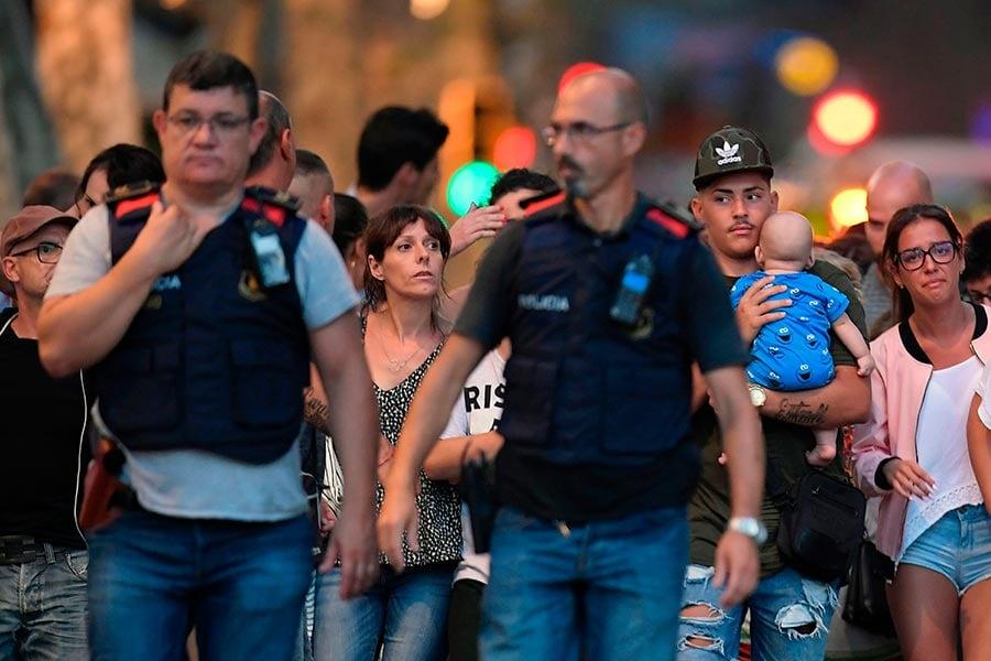 警方人員陪同現場民眾走出戒嚴區。(LLUIS GENE/AFP/Getty Images)