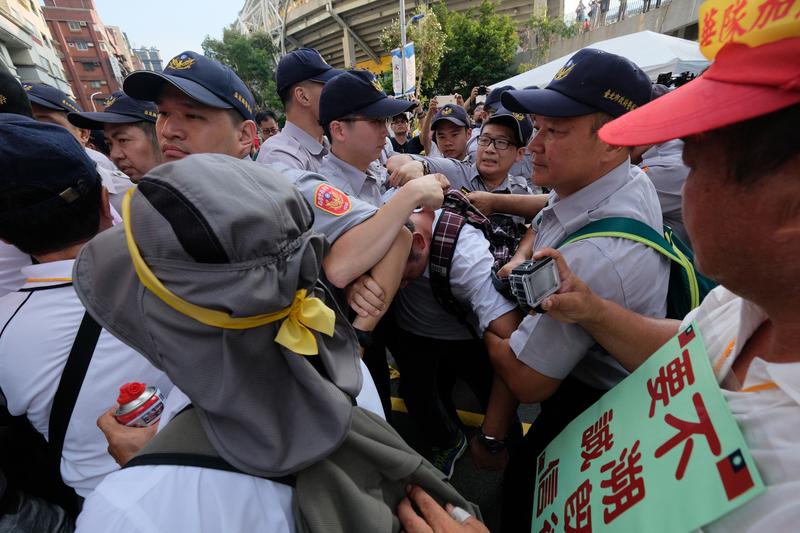 台北世大運19日晚間將在台北田徑場開幕,場外下午有退休警察前往抗議,與維安警方發生推擠。(中央社)