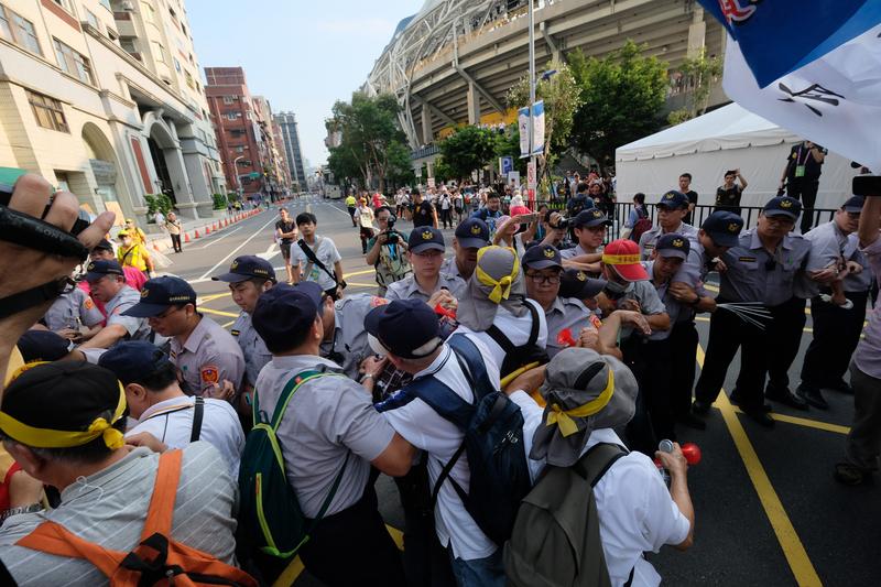 台北世大運19日晚間將在台北田徑場開幕,場外下午有退休警察前往抗議,與維安警方發生推擠。 (中央社)