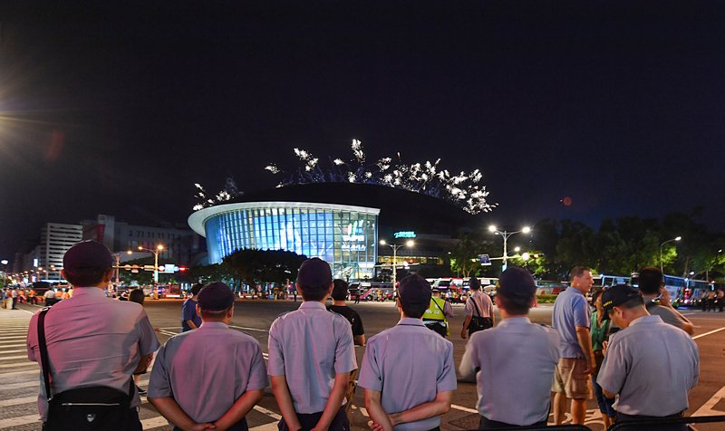 2017台北世大運19日晚間在台北田徑場舉行開幕式,場外大批員警協助維安。當場內施放煙火宣告儀式圓滿落幕,場外不少員警也被美麗煙花吸引,遠眺場館。(中央社)