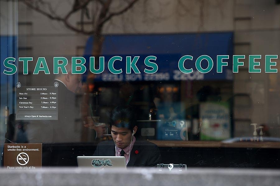 你可能會認為在忙碌的咖啡店或大酒店裏上Wi-Fi會很安全,但實際上任何公共Wi-Fi都是不安全的。圖為一名男子正在星巴克咖啡店內使用手提電腦。(Justin Sullivan/Getty Images)
