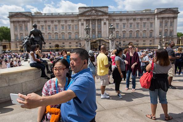 白金漢宮、議會大廈、首相府等地是中國遊客來英的必去地點。圖為中國遊客在白金漢宮門前留影。(Rob Stothard/Getty Images)