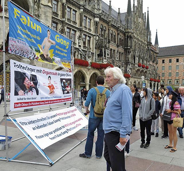 8月12日,德國慕尼黑(Munich)的部份法輪功學員在市政廳前的瑪琳廣場(Marienplatz)上設立法輪功真相展位。有人當場跟法輪功學員學煉功法。民眾也紛紛加入譴責中共對法輪功學員迫害的行列中。