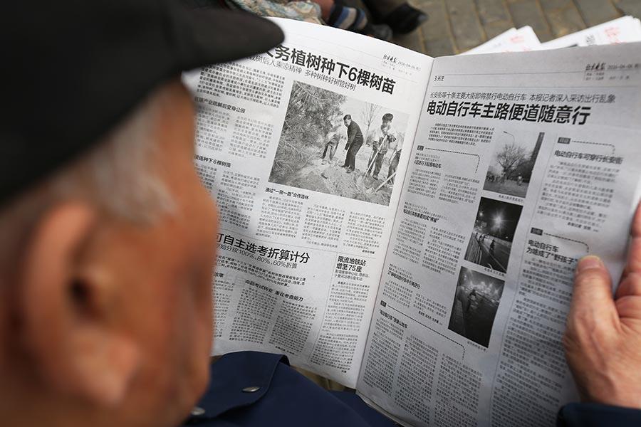 圖為一名老人正在閱讀報紙。(STR/AFP/Getty Images)