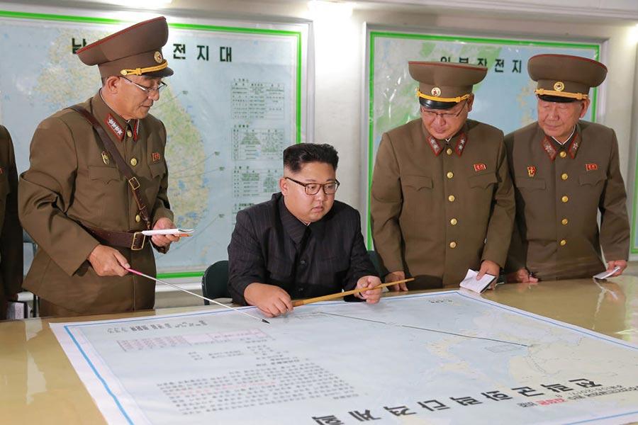 南韓「每日北韓」網站報道說,北韓平壤一棟政府大樓被發現有反對該國領導人金正恩的塗鴉。圖為金正恩(中坐者)資料圖片。(STR/AFP/Getty Images)