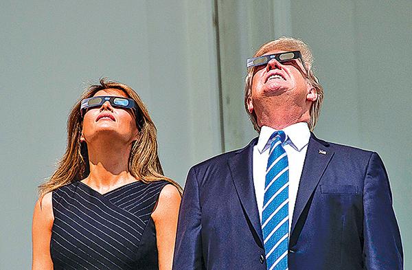 總統特朗普和第一夫人在白宮。特朗普過程中還一度不帶護目鏡直接看太陽,讓助手們急忙發聲警告。(AFP)