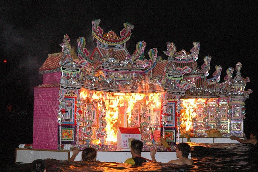 台灣基隆中元祭放水燈,將水燈頭奮力送入海中,並燒旺漂遠。(中央社)
