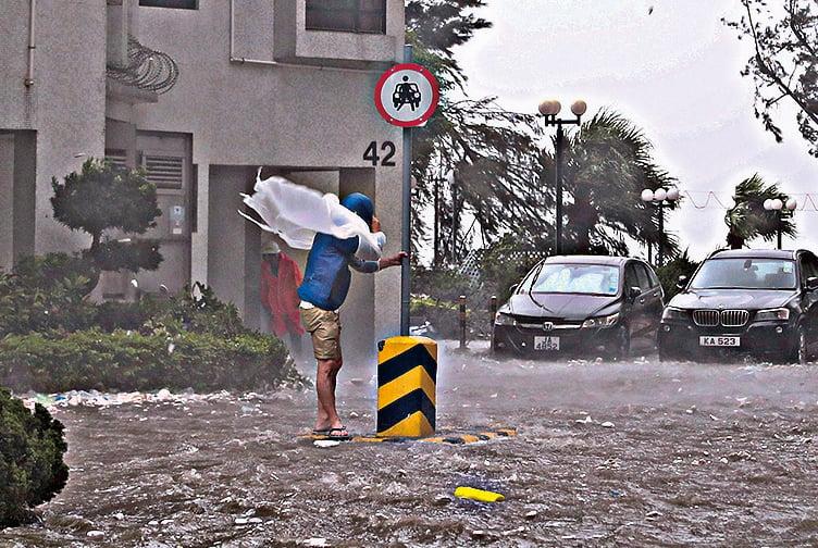 現場所見,杏花邨內馬路變成一條河流,水深一度及膝。市民要扶著電線杆等才能站立,否則都被風吹倒。(余鋼/大紀元)