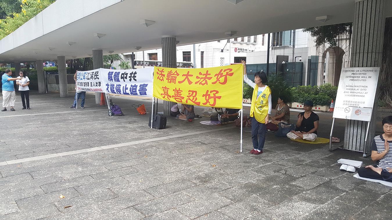 8月22日傍晚,部份法輪功學員如常在遮打花園舉行和平請願反對迫害,但遭到康文署人員多番阻撓展示橫幅。(受訪者提供)