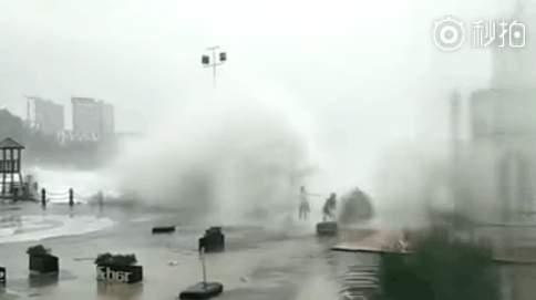 路人被颱風掀起的海浪打倒。(網絡圖片)