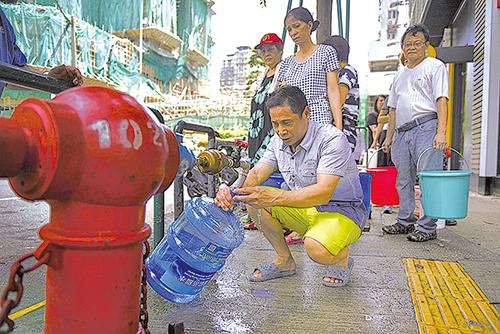 由於澳門仍停水停電,市民要用到街上輪候取水,甚至在消防喉取水。(澳門危險駕駛fb、Getty Images)